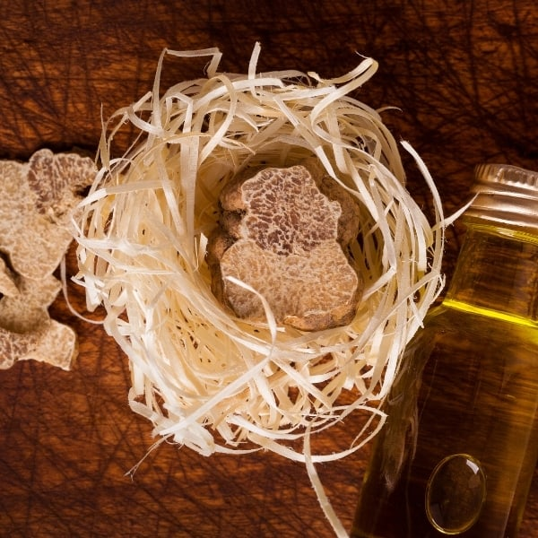 Image of white truffle in a nest with a bottle of oil next to it representing White Truffle Pure Olive Oil