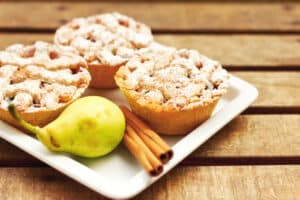 Closeup of mini pies on a plate decorated with cinnamon and a pear