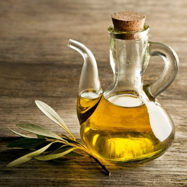 photo of jar of olive oil with a leaf on wood table representing Koroneiki Extra Virgin Olive Oil