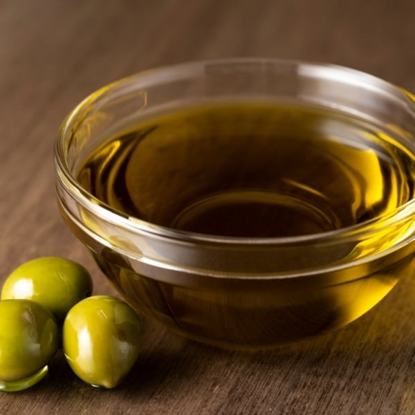 Photo of clear glass dish of olive oil with green olives next to it representing Organic Nocellara