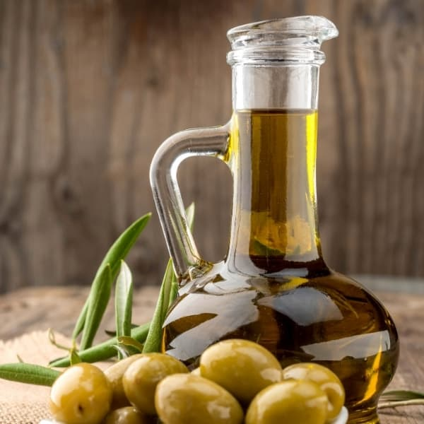 Photo of glass pouring jar of olive oil with green olives next to it representing Organic Picual Extra Virgin Olive Oil