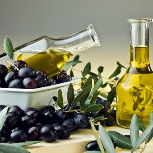 photo of two bottles of olive oil surrounded by olives and leaves representing Picholine Extra Virgin Olive Oil