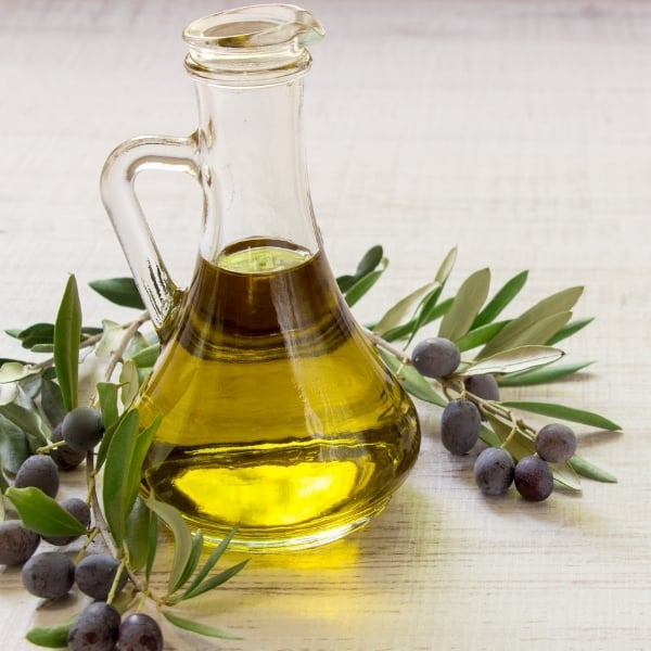 photo of jar of olive oil with branches and black olives around it representing Arbequina Extra Virgin Olive Oil