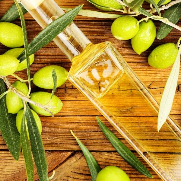 Photo of glass bottle of olive oil on wood table surrounded by green olives and olive branches representing Organic California Arbosana Extra Virgin Olive Oil
