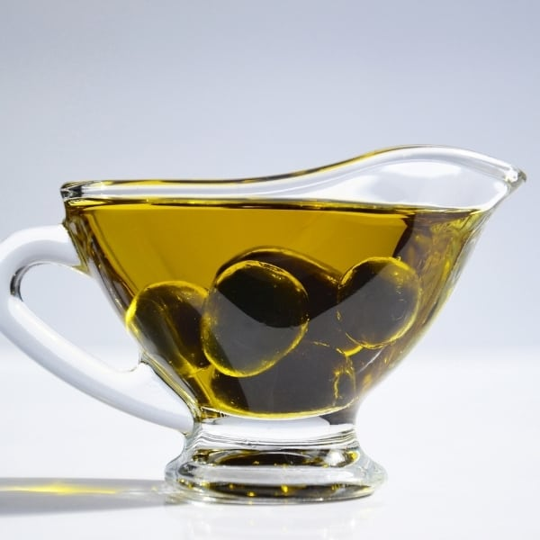 photo of pitcher of olive oil with olives in it representing Coratina Gran Cru Extra Virgin Olive Oil