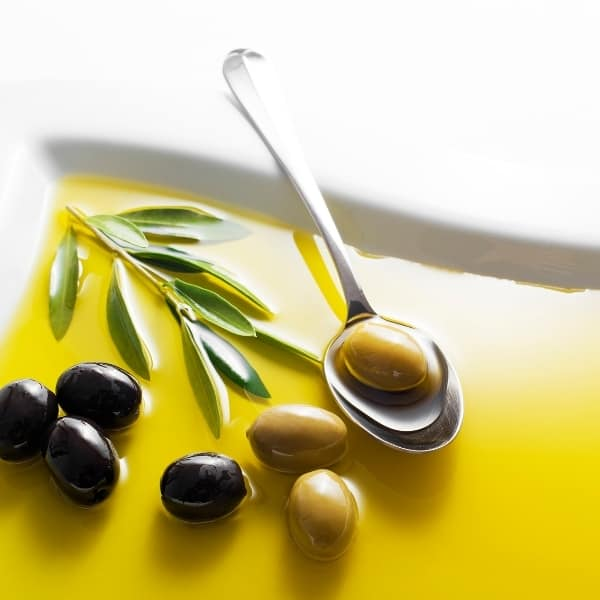 photo of white plate with olive oil on it and a spoon and olives representing Leccino Extra Virgin Olive Oil