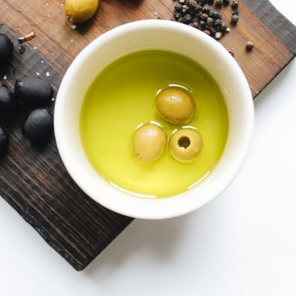 photo of bowl of olive oil with olives in it sitting on chopping board representing Organic Barnea Extra Virgin Olive Oil
