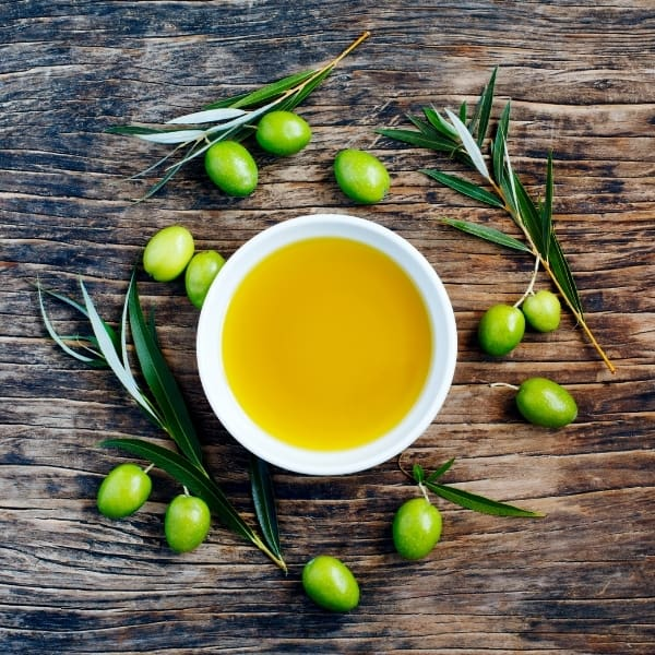 photo of bowl of olive oil on wood table with green olives and leaves around it representing Arbosana Extra Virgin Olive Oil