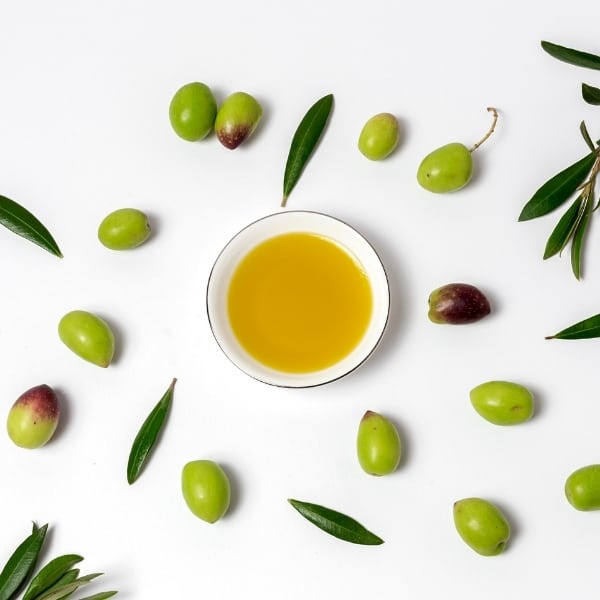 "photo of bowl of olive oil surrounded by olives and leaves representing ""Oro Bailen"" Arbequina Extra Virgin Olive Oil"