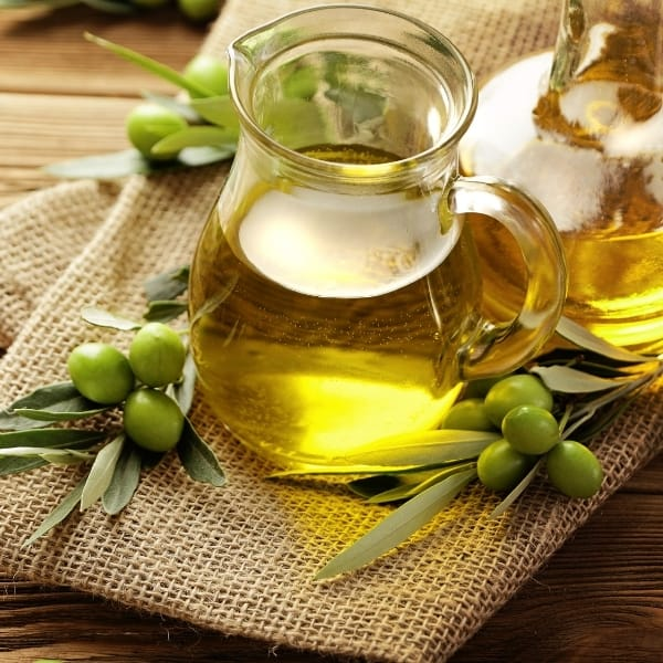 photo of jar of olive oil with green olives and leaves next to it representing manzanillo extra virgin olive oil