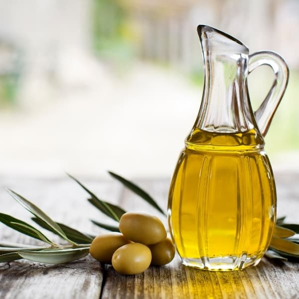 photo of jar of olive oil with olives and leaves next to it representing picual reserve extra virgin olive oil