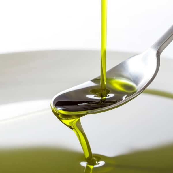photo of olive oil being poured into spoon over a bowl of olive oil representing mission extra virgin olive oil