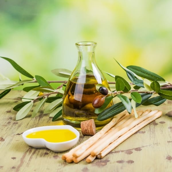 photo of olive oil in jar, heart shaped bowl of olive oil, breadsticks and olive branches on wood table representing Organic Arbequina Extra Virgin Olive Oil