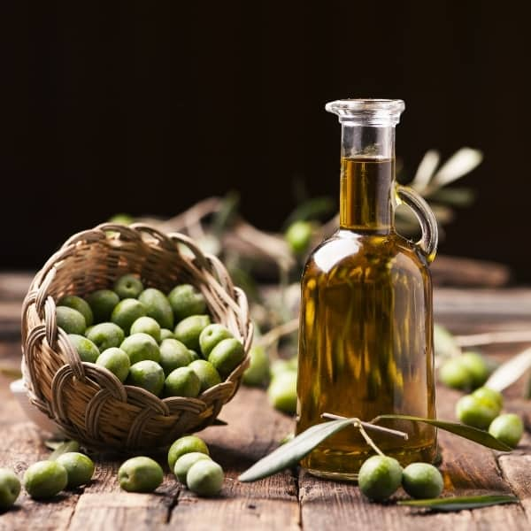 photo of bottle of olive oil with olives in basket representing ogliarola extra virgin olive oil