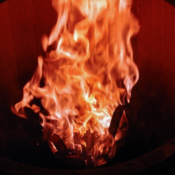photo of wood barrel on fire representing olive wood smoked flavored olive oil