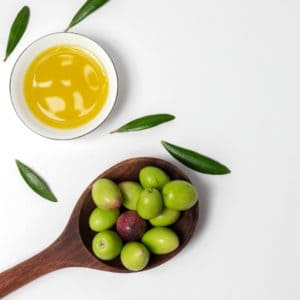 photo of bowl of olive oil and spoon with olives representing hojiblanca extra virgin olive oil