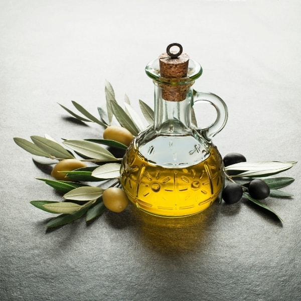 photo of jar of olive oil with olives and olive branches representing melgarejo picual extra virgin olive oil