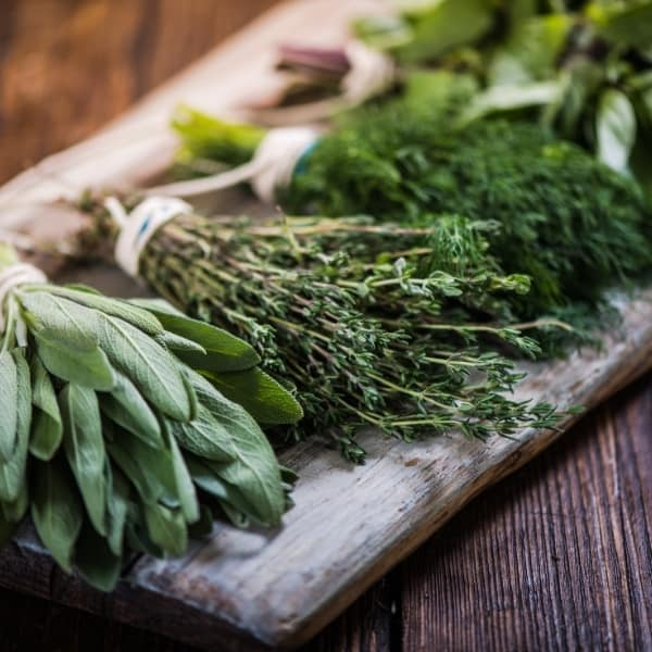 photo of bunches of herbs on wood board representing Tuscan herb olive oil