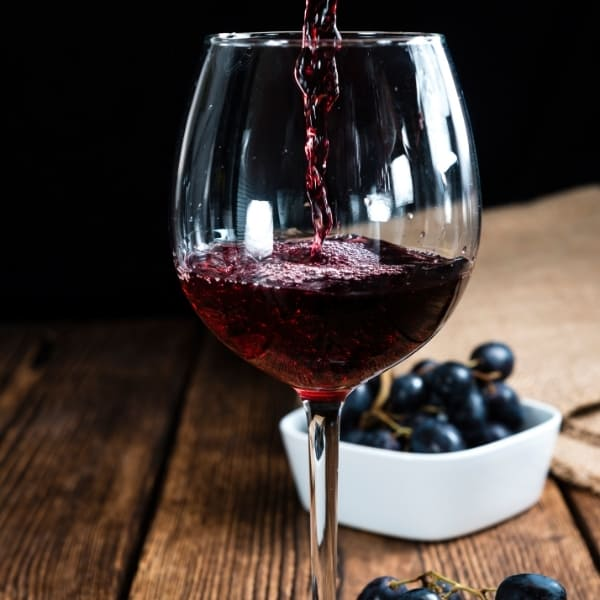 photo of red wine being poured into glass with grapes in background representing organic red wine vinegar