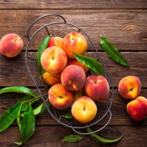 photo of peaches in wire basket representing peach white balsamic vinegar
