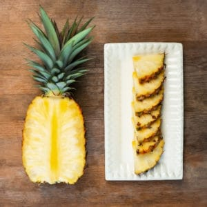 photo of half a pineapple and pineapple slices on plate representing pineapple white balsamic vinegar