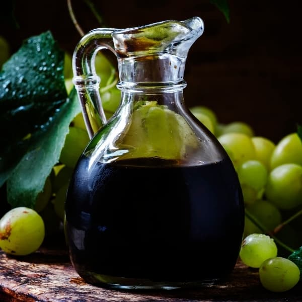 photo of jar of balsamic vinegar with grapes in background representing traditional aged 18 years balsamic vinegar