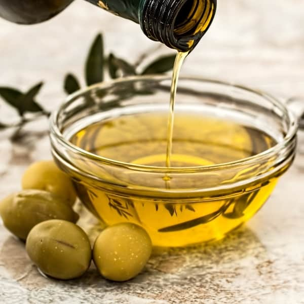 photo of olive oil in dish and green olives representing athinolia olive oil