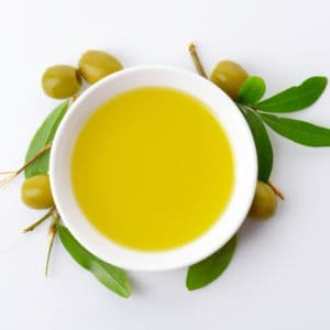 photo of bowl of olive oil surround by olives representing coratina extra virgin olive oil