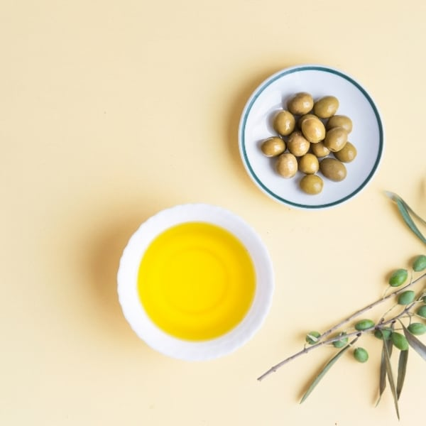 photo of bowls of olive oil, olive branch, and green olives representing favolosa extra virgin olive oil