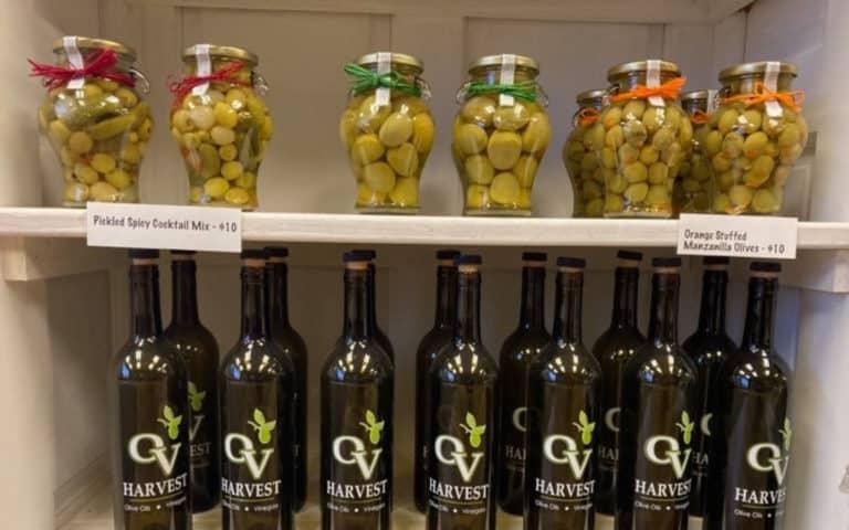 ov harvest gourmet olives in jars on shelf and ov harvest glass bottles on shelf