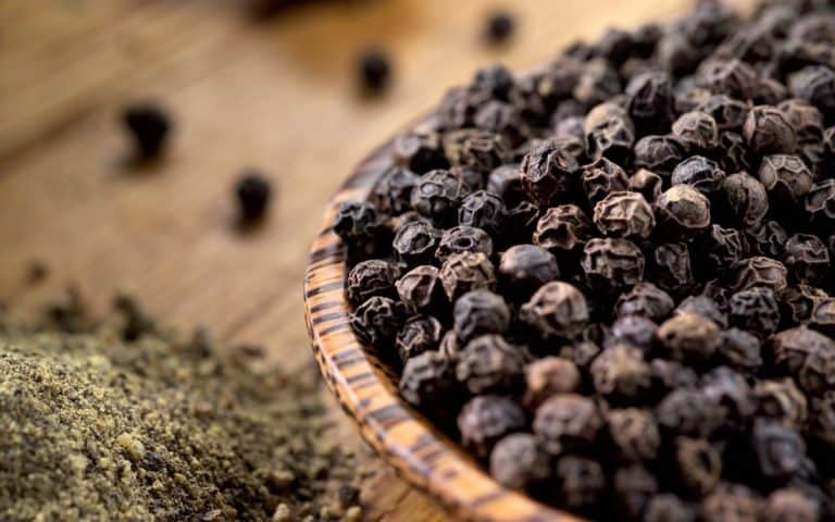 Image of black peppercorns in bowl representing OV harvest Madagascar Black Pepper Olive Oil